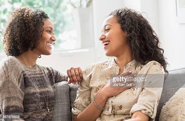 laughing women talking on sofa - zus stockfoto's en -beelden