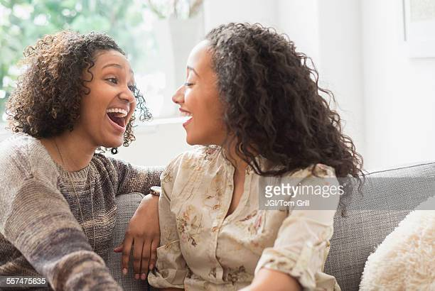 laughing women talking on sofa - sister stock pictures, royalty-free photos & images