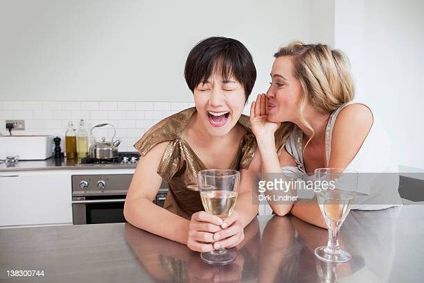 Laughing women whispering in kitchen