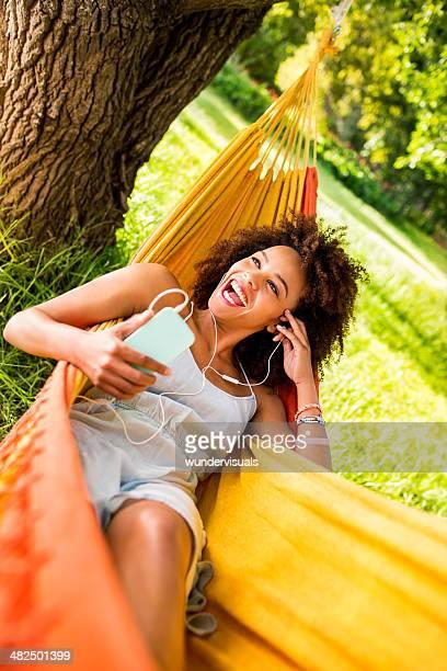 Laughing young african american woman enjoying music