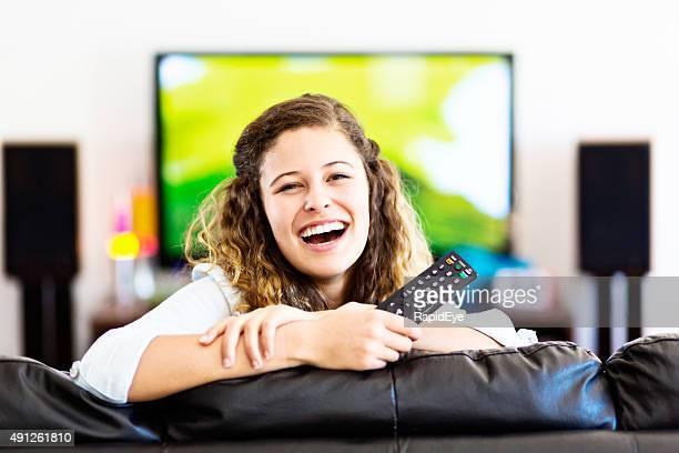 Lachen, junge Schönheit mit Fernbedienung rauskommt von TV-Bildschirm