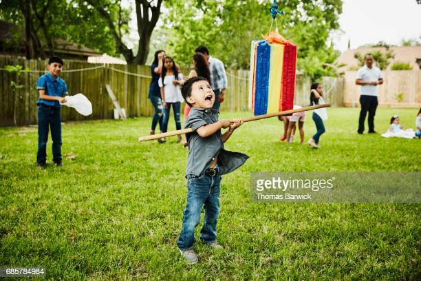 laughing young boy trying to break open pinata during family birthday party - pinata stock pictures, royalty-free photos & images