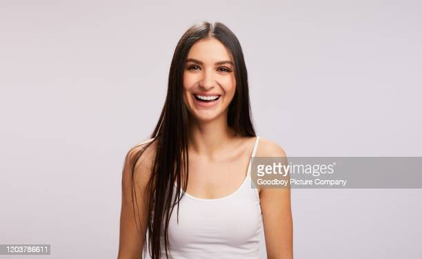 laughing young brunette woman standing against a gray background - tank top stock pictures, royalty-free photos & images