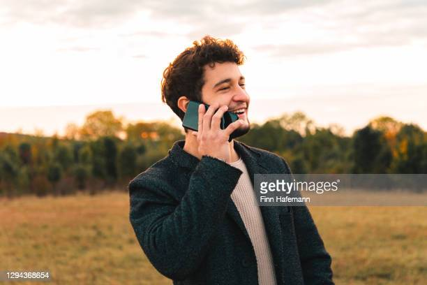 lachender junger geschäftsmann mit einem telefonat im freien auf dem handy - lässig schicker stil stock-fotos und bilder