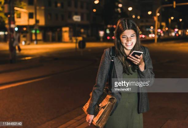 laughing young businesswoman with leather bag on the phone at night - junge frau allein stock-fotos und bilder