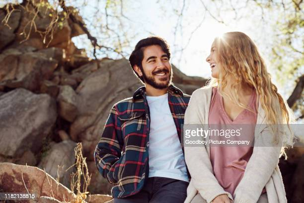 laughing young couple enjoying a sunny day out in nature - heterosexual couple stock pictures, royalty-free photos & images