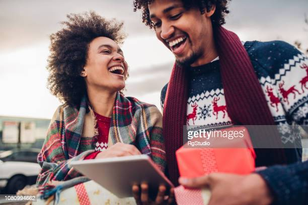 Laughing young couple online shopping for Christmas presents