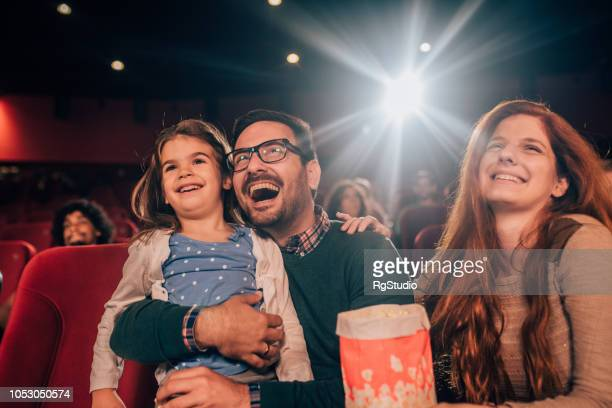 laughing young family at cinema - children theatre stock photos and pictures