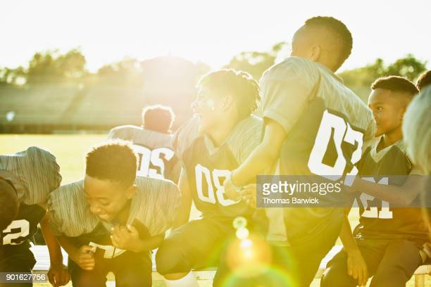 Laughing young football teammates gathered together after football game
