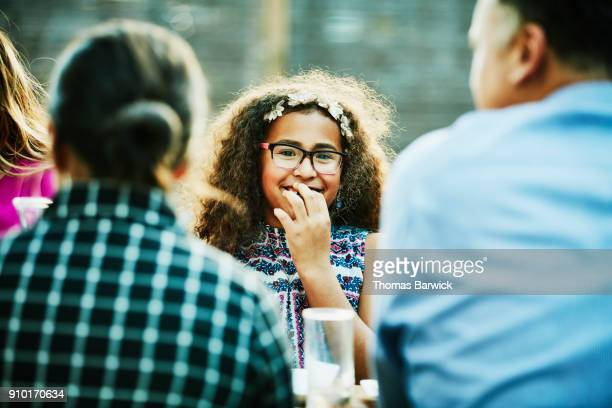 laughing young girl at outdoor dinner party with family and friends - naughty america stock pictures, royalty-free photos & images