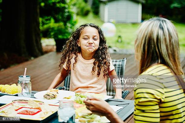laughing young girl eating dinner with family - funny black girl stock photos and pictures