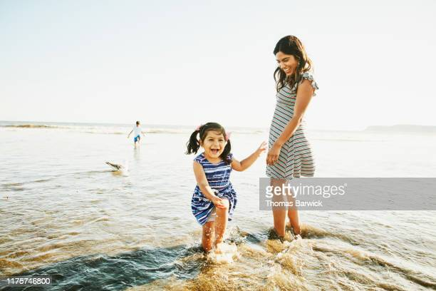 laughing young girl playing in surf with mother and brother - paradise stock pictures, royalty-free photos & images