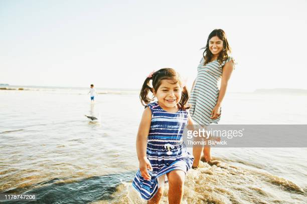 laughing young girl running out of water while playing in surf with mother - latin american and hispanic stock pictures, royalty-free photos & images