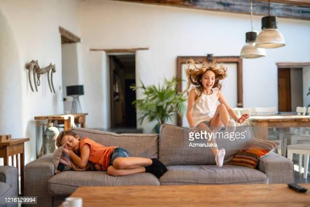 ragazza che ride sorprendente ragazzo addormentato sul divano - solo bambini foto e immagini stock