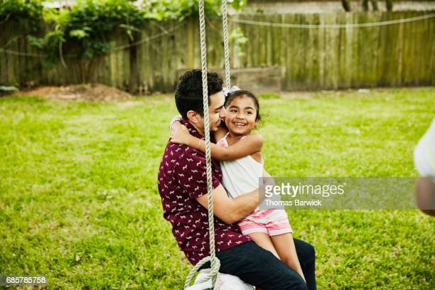 Laughing young girl swinging on swing with uncle during family party