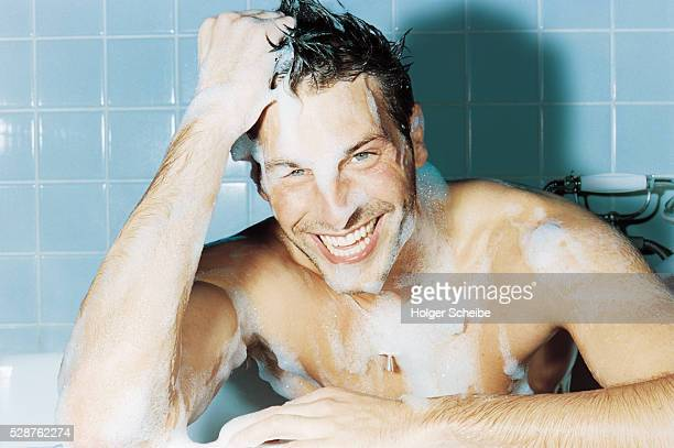 Laughing young man covered with lather