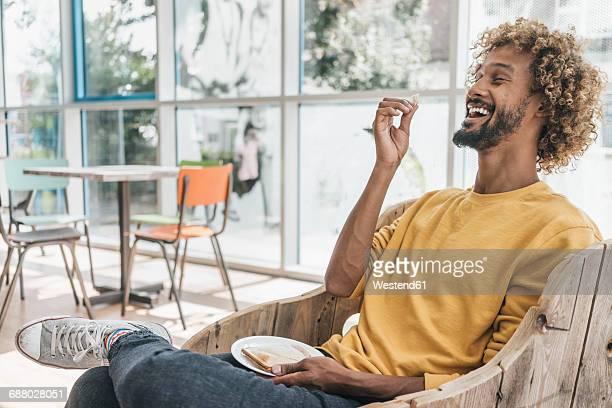 laughing young man eating sandwich - üppig allgemein beschreibender begriff stock-fotos und bilder