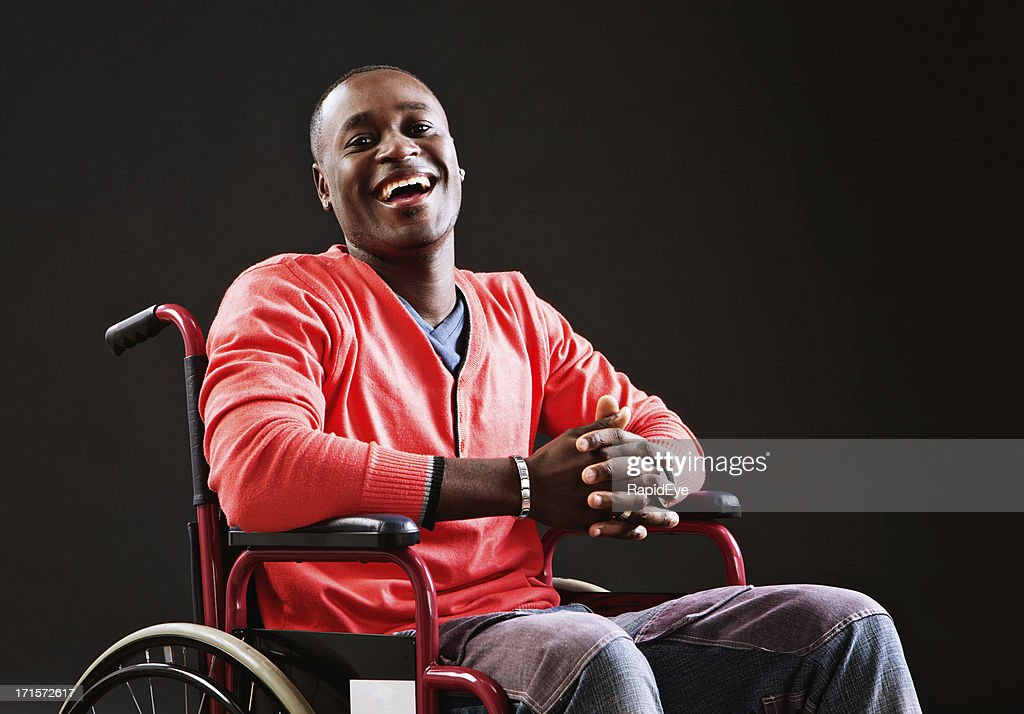 Laughing young man in wheelchair accepts his situation : Stock Photo
