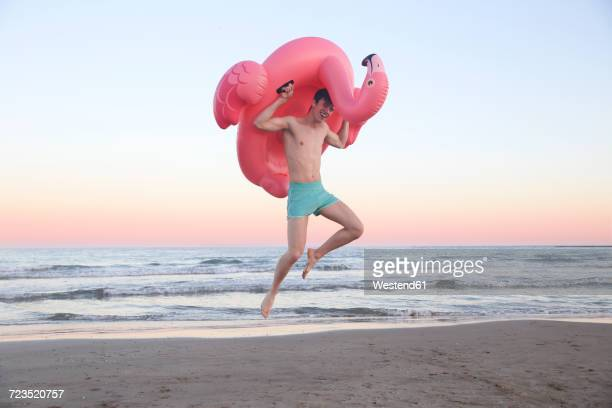 Laughing young man jumping in the air on the beach with inflatable pink flamingo