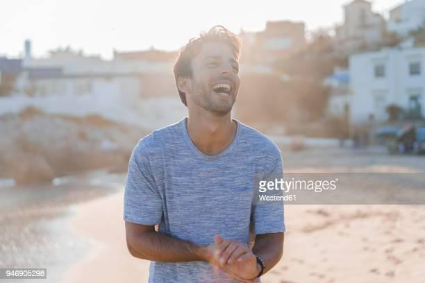 laughing young man on the beach at sunset - homens gostosos imagens e fotografias de stock