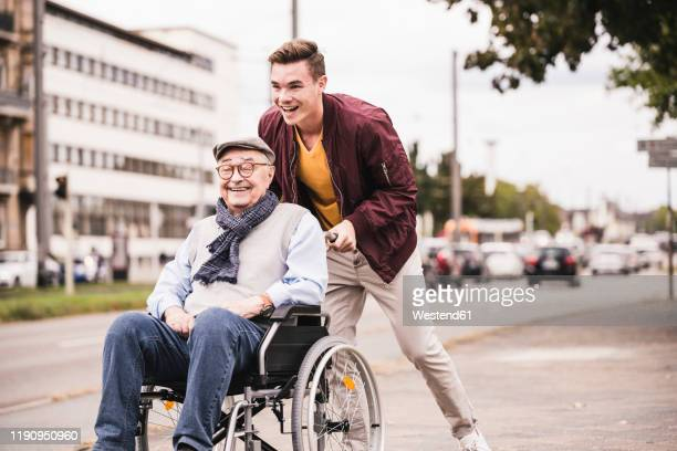 laughing young man pushing happy senior man in wheelchair - care stock pictures, royalty-free photos & images