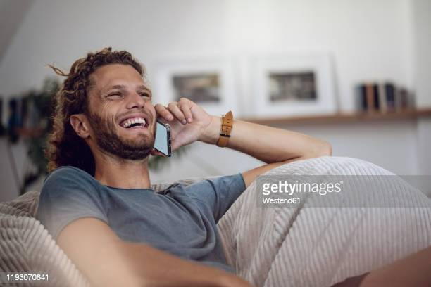 laughing young man relaxing in beanbag at home talking on the phone - am telefon stock-fotos und bilder
