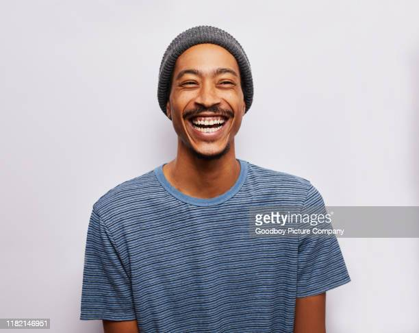 laughing young man standing against a gray background - laughing stock pictures, royalty-free photos & images