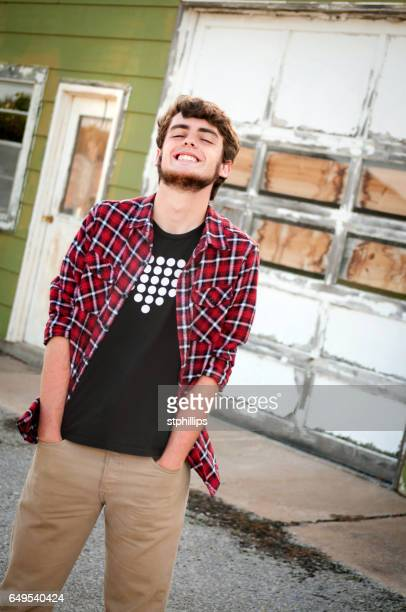 Laughing Young Man Standing Outside of a Dilapidated Building