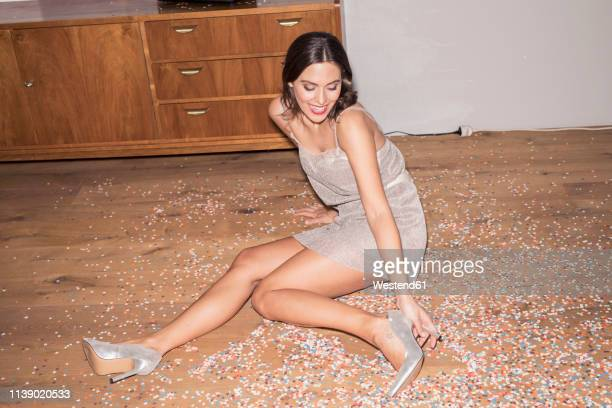 laughing young man wearing silver high heels and evening dress sitting on the floor in between confetti - silver shoe stock photos and pictures