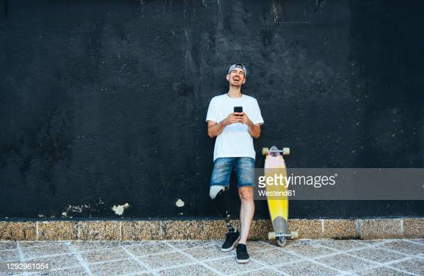 laughing young man with leg prosthesis and skateboard using smartphone - disability stock pictures, royalty-free photos & images