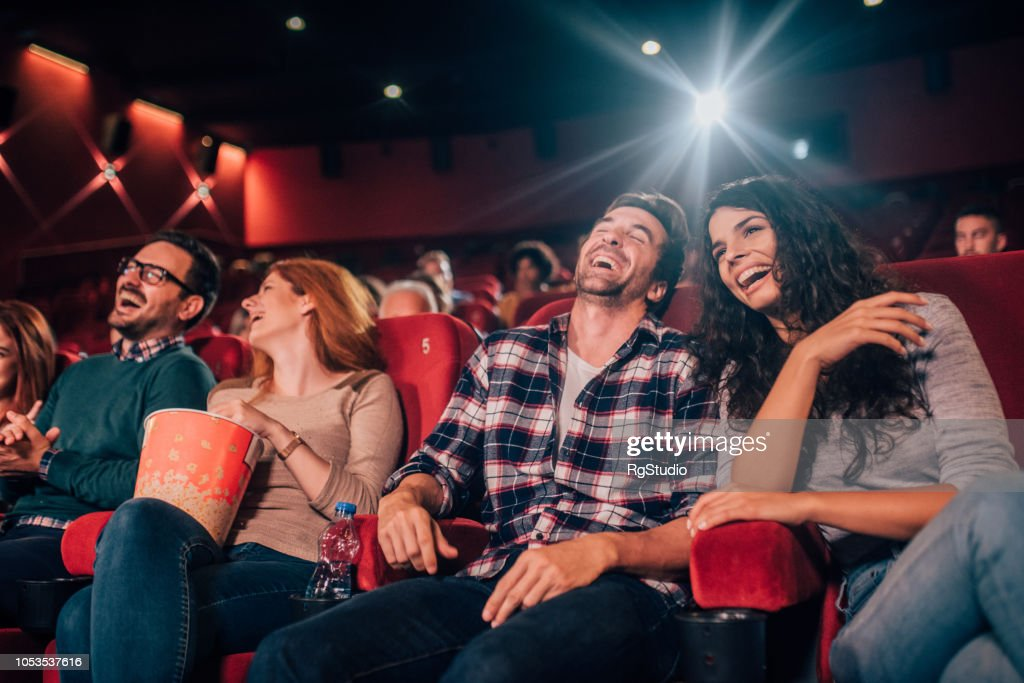 Laughing young people at cinema : Stock Photo