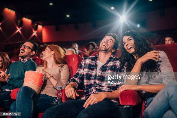 laughing young people at cinema - film industry stock pictures, royalty-free photos & images