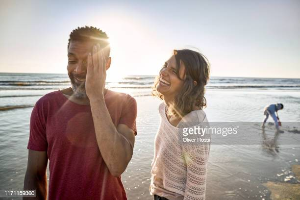 laughing young woman and mature man on the beach - carefree stock pictures, royalty-free photos & images