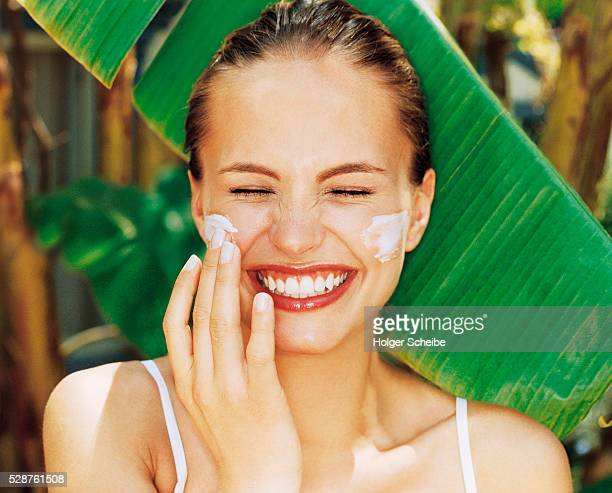 Laughing young woman applying cream on her cheek