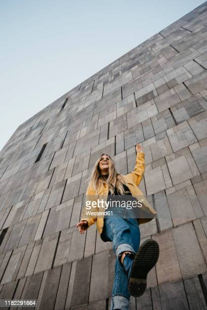 laughing young woman balancing on one leg, vienna, austria - low angle view stockfoto's en -beelden