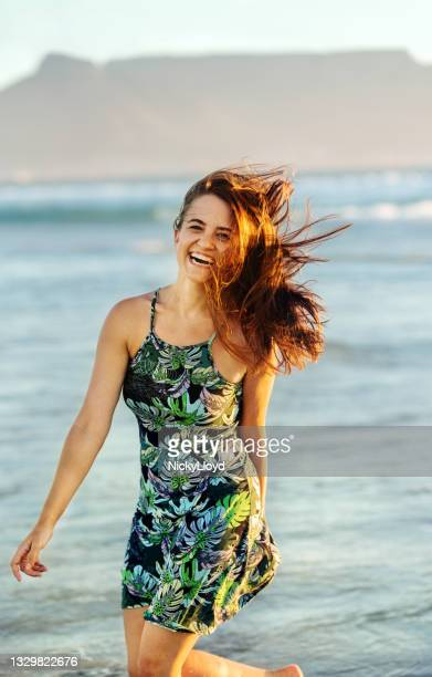 carefree young woman laughing while walking
