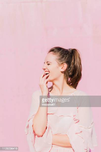 laughing young woman in front of pink wall - chemisier blanc photos et images de collection