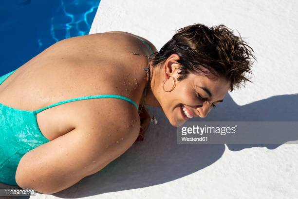 laughing young woman leaning at poolside - femme pulpeuse photos et images de collection