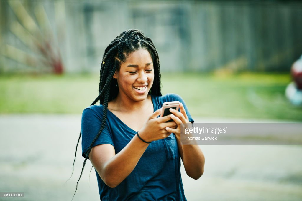Laughing young woman looking at smartphone on summer evening : Stock Photo