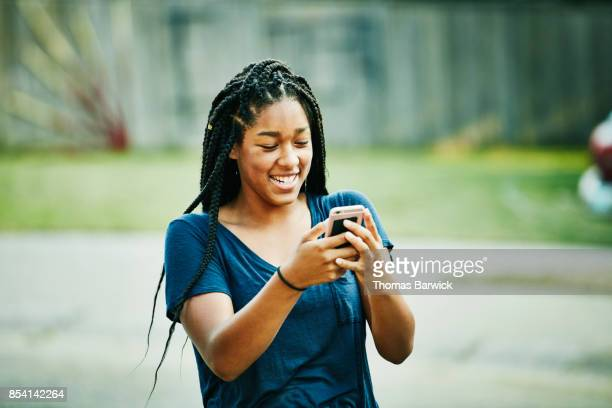 laughing young woman looking at smartphone on summer evening - funny black girl stock photos and pictures