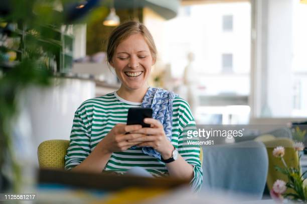 laughing young woman looking on cell phone in a cafe - candid forum stock-fotos und bilder