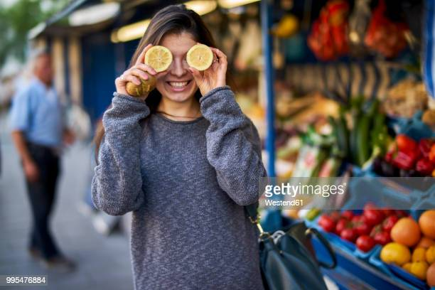 laughing young woman on market covering her eyes with lemon halves - tropische frucht stock-fotos und bilder