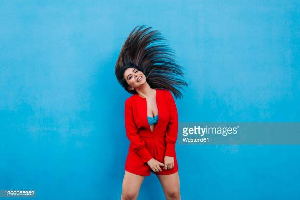 laughing young woman shaking her head in front of blue wall - blue jumpsuit stock pictures, royalty-free photos & images