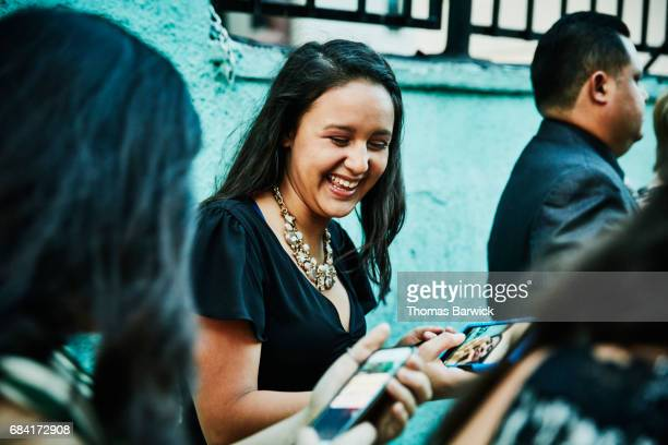 Laughing young woman showing photo on smartphone to friend during celebration dinner
