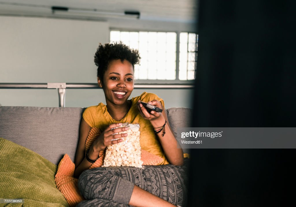 Laughing young woman sitting on couch watching Tv : Stock Photo