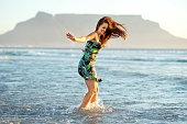 carefree young woman laughing while splashing