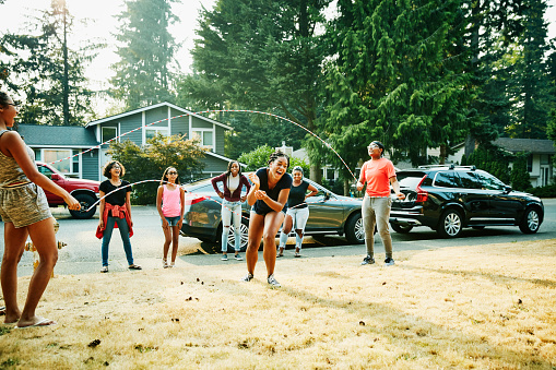 Laughing young woman trying to double dutch jump rope with friends on summer evening - gettyimageskorea