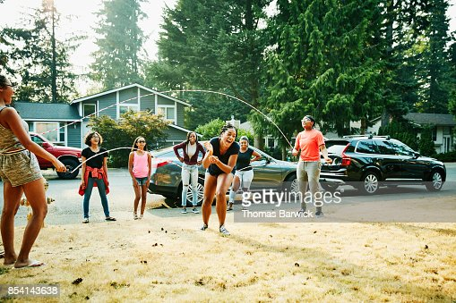Laughing young woman trying to double dutch jump rope with friends on summer evening