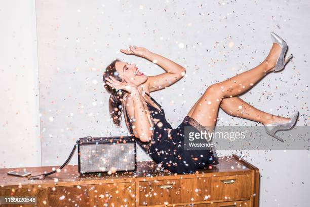laughing young woman under shower of confetti at a party - flying solo after party bildbanksfoton och bilder
