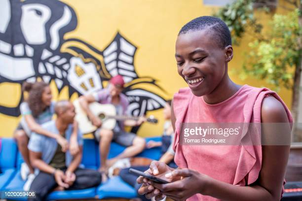 laughing young woman using cell phone with friends and graffiti wall in background - petit groupe de personnes photos et images de collection